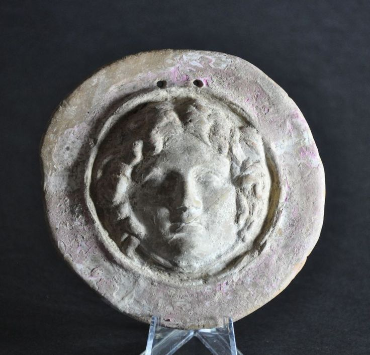 Greek Canosan Gorgon applique, 4th century B.C. Polychrome Canosan applique showing facing head of Medusa with traces of original pink and white pigments surviving, two holes for hanging, 10.3 cm diameter. Private collection