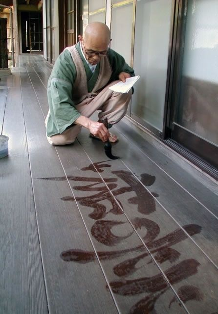 Monk, writing words with water.