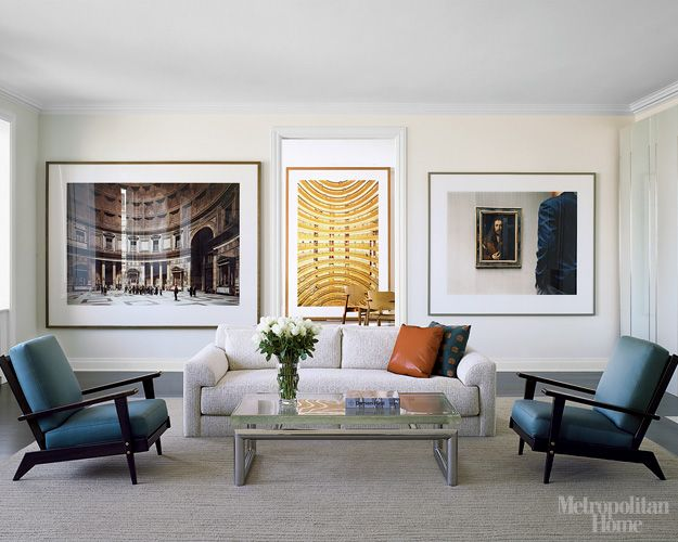 Molduras enormes ocupam a parede toda. O quadro do meio fica em outro ambiente, mas o alinhamento com a porta deixa a impressão de proximidade. Via Metropolitan Home.