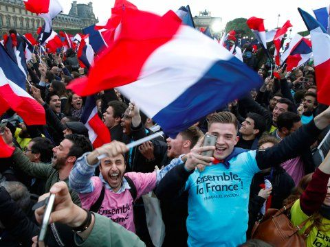 Supporters of French President Elect Emmanuel Macron celebrate near the Louvre museum after early results were announced in the second round vote in the 2017 presidential elections in Paris, France, May 7, 2017.