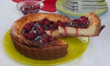 A cheesecake de framboesa é redonda e está sobre um prato redondo de vidro de cor amarela. Um pedaço está sendo retirado, sendo possível ver o interior. Na parte de cima há a geleia de framboesa vermelha e framboesas inteiras.