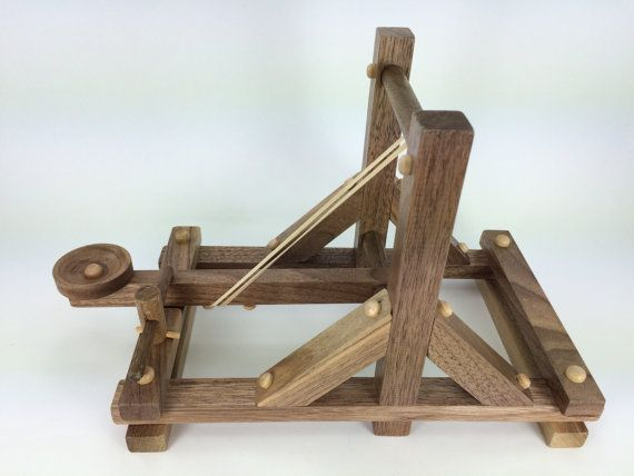 Our wooden toy catapult will throw a small item anywhere from three to 12+ feet. It is powered by a common rubber band, which is easily