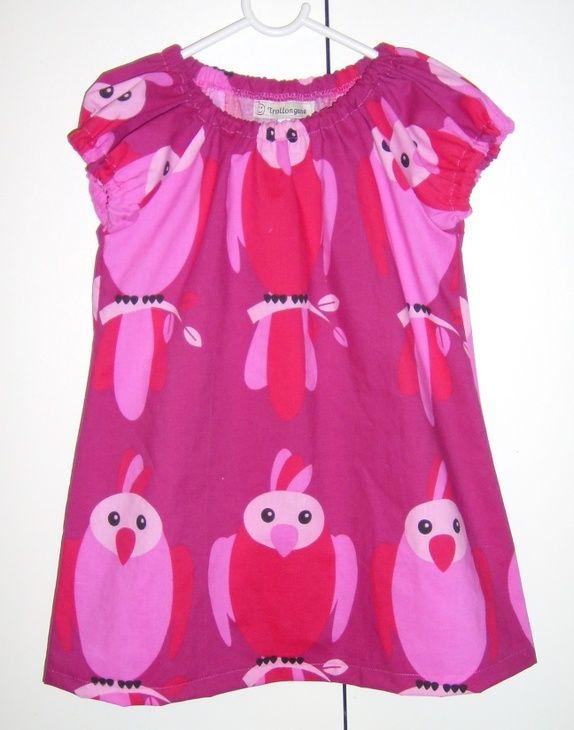 Kjole med papegøyer på str 104  Kjolen vokser med barnet og kan brukes som tunika senere.    Kjolen er laga av 52% polyester og 48% bomull   Kan vaskes på 40 grader