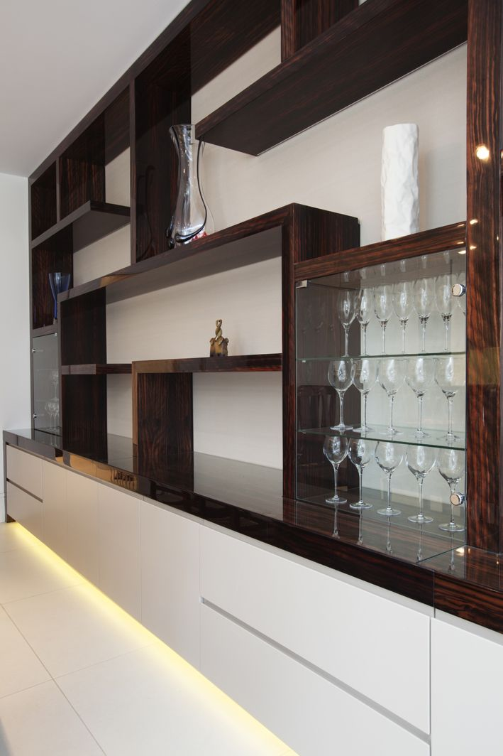 bespoke dark wood shelving unit with glass shelve section over modern handleless wide base units