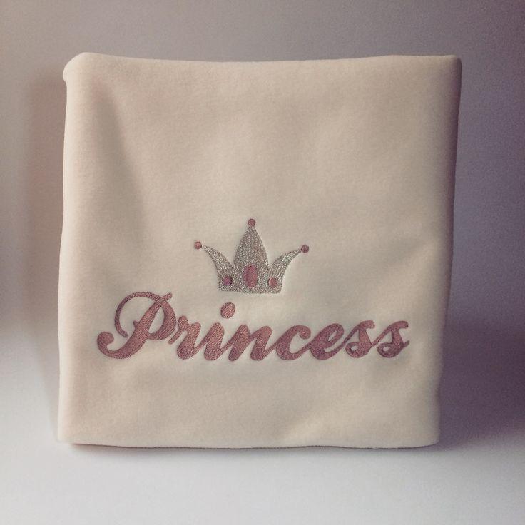 Morbidissima copertina in pile beige, impreziosita da un ricamo rosa con scritta Princess e da una corona.