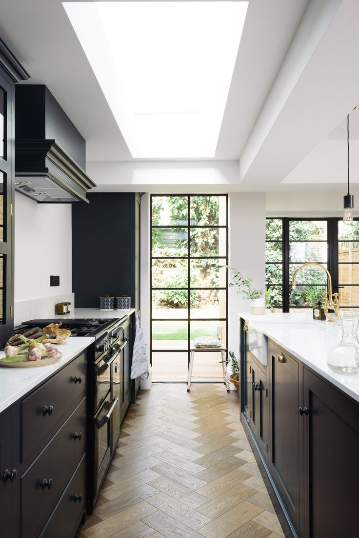 Light worktops, deep blue cupboards and big Crittall style windows make this kitchen feel spacious and airy