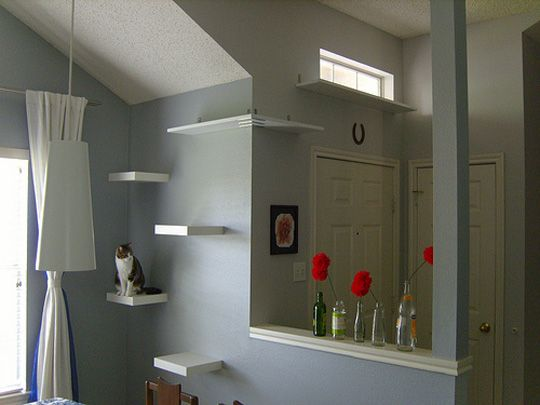 "I love these simple cat climbing shelves posted over at Saucy Dwellings. They used Ikea Lack shelves with a custom made shelf that wraps around the corner and leads to a window shelf over the front door. Brilliant! *They don't look like ""cat climbing shelves"", they just look like a nice shelving display! ; )"