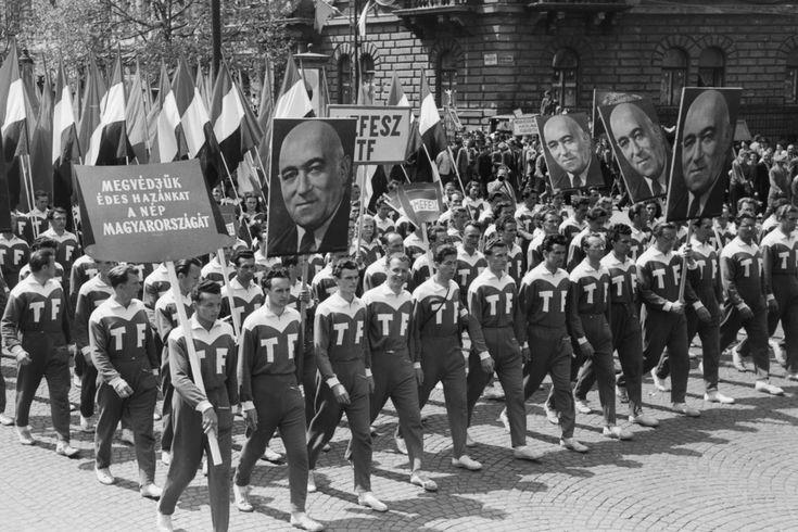 Május elsejei felvonulók az Andrássy úton, a Köröndnél. A tér 1938 és 1945 között Adolf Hitler nevét viselte, 1971-től Kodály körönd. Az Andrássy út a koalíciós időkben nem vesztette el nevét, 1950-ben Szálin út, a forradalom napjaiban Magyar Ifjúság útja, 1957-től Népköztársaság út. A képen a testnevelési főiskolások vonulnak Rákosi Mátyás a kommunista párt főtitkárának portréjával.