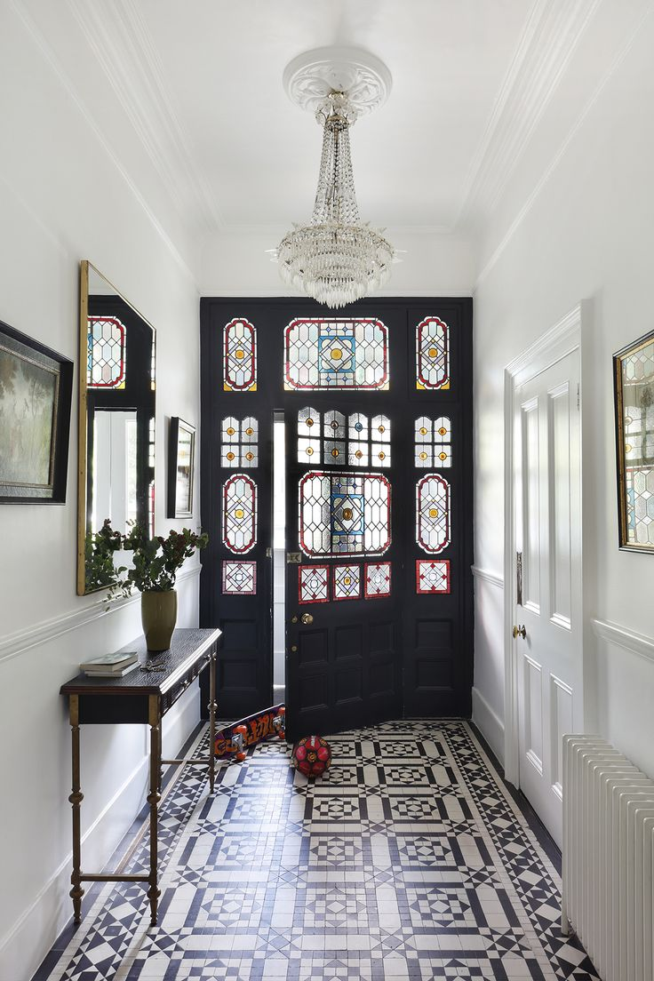 This modern hallway is flooded with light thanks to the stained glass in the door, which perfectly compliments the tiled floor in this stunning urban home. The modern hallway design is complemented with framed pictures and a statement light feature.  #HallwayIdeas #HallwayDecorating #ModernHallwayIdeas