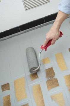 A l'aide d'un rouleau laqueur, répartir la peinture avec des passes croisées - Repeindre le carrelage au sol d'une cuisine - CôtéMaison.fr
