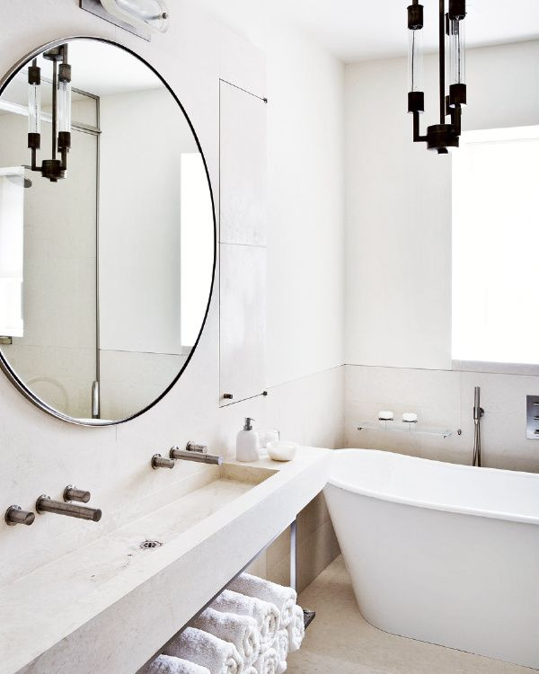A former warehouse turned into an elegant, eclectic home | freestanding tub, modern sink, round mirror.