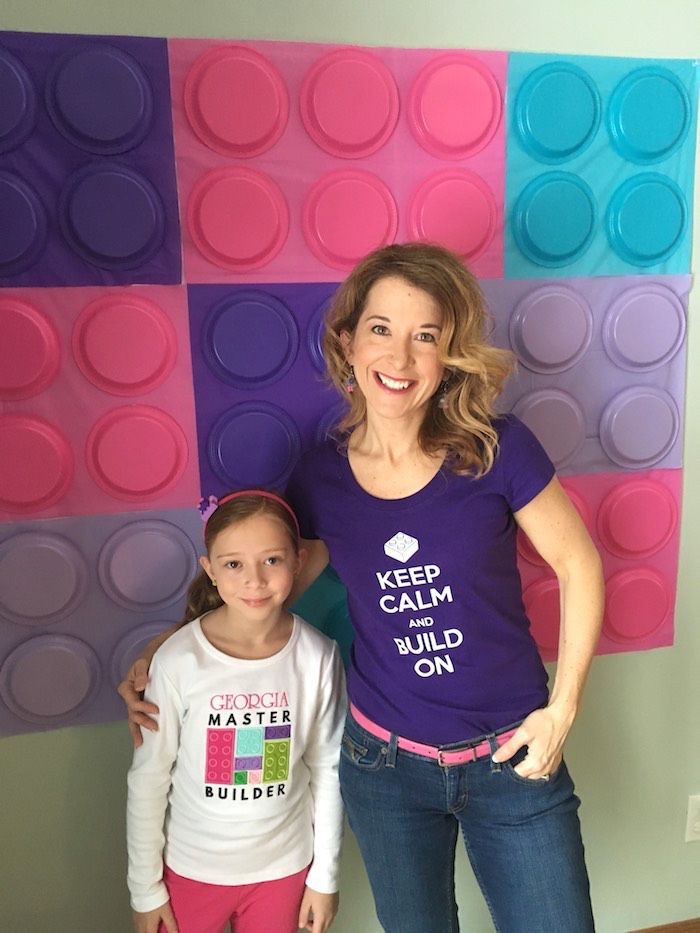 Me and Georgia in front of our plastic plate and tablecloth backdrop.  I used a solid white tablecloth..higher grade plastic to double side tape the other colors to.  Lego Backdrop + Birthday Girl from a Girl Themed Lego Party via Kara's Party Ideas | KarasPartyIdeas.com (37)