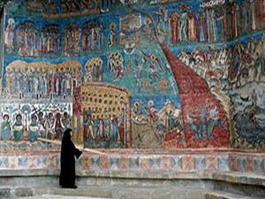 Painted monastery wall and nun