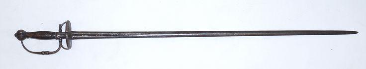 Een ijzeren degen, kling deels opengewerkt, stootplaat met decor van man en vrouw in cartouce, houten greep en gecanneleerde pommel met acanthusblad motieven aan de rand, ca. 1750