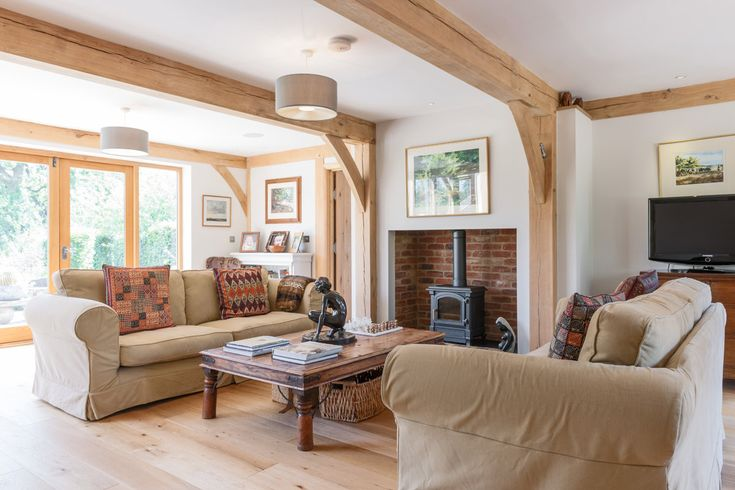 Post and beam style oak frame adds character to this lounge. Less is sometimes more with exposed oak frame and this is a perfect way to add character to a room using oak frame in a more contemporary way. www.welshoakframe.com #oakframe #loungeideas #exposedbeams #openplanlounge