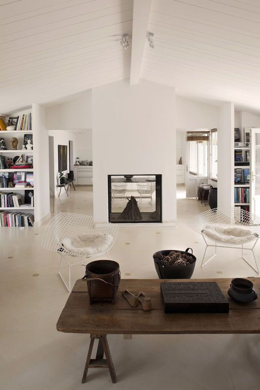 Drewniany stół z odzysku to jedyny stary element w tym wnętrzu. Pozostałe meble to tylko krzesła vintage i półki wykorzystujące układ architektoniczny domu i wykorzystujące istniejące ścianki po obu stronach kominka. Uwagę przyciąga nowoczesny kominek - zabudowano go taflą szkła, przez którą można zajrzeć do sąsiedniego pomieszczenia.