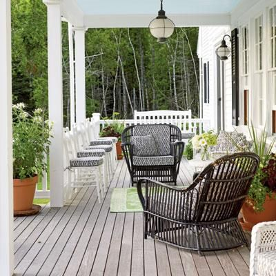An abundant array of seating makes for a warm and inviting porch to enjoy with friends and neighbors. A lime green rug and planters add a touch of color and celebrate the surrounding foliage.  coastalliving.com