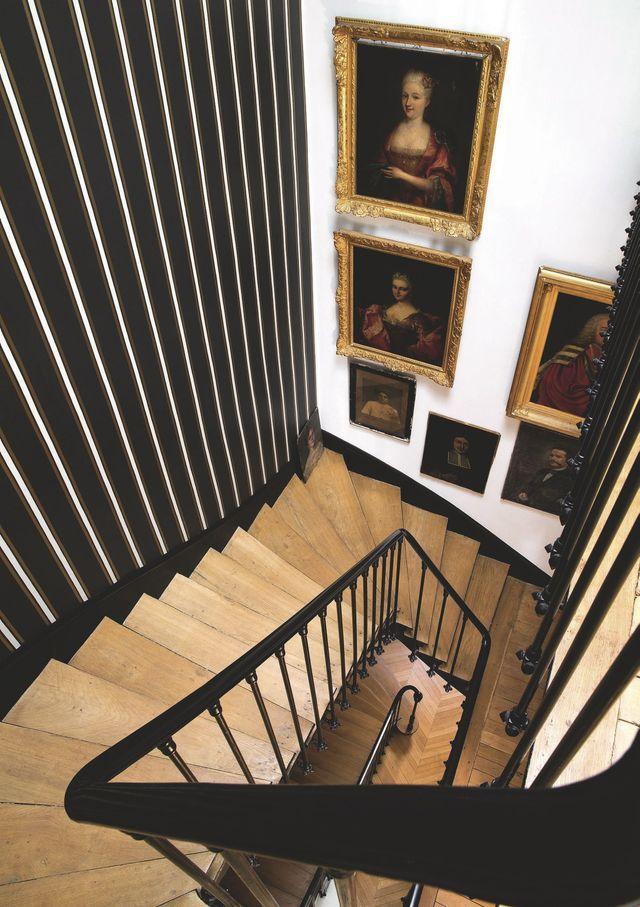 """L'escalier central habillé de papier peint """"Ray Pietra"""", Dedar, dessert les deux étages. Sur le mur, portraits de famille et d'autres chinés."""