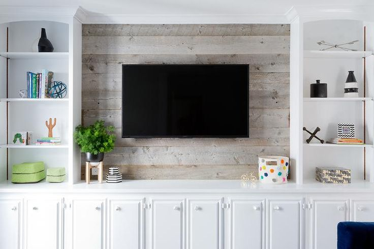 Styled white built in cabinets flank a barn board wall fitted with a flat panel television mounted above white TV cabinets.