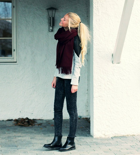 Aurora Mohn in a grey leather patch sweater, grey acid wash skinnies, burgandy knit scarf and black chelsea boots.