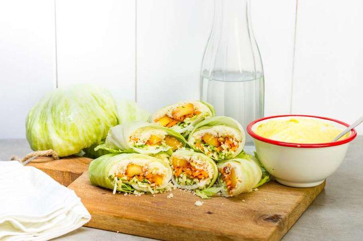 Recept voor sla-wraps voor 4 personen. Met zout, peper, ijsbergsla, yoghurt, perzik, courgette, couscous, pijnboompitten, geraspte wortel, kerriepoeder, honing en citroen