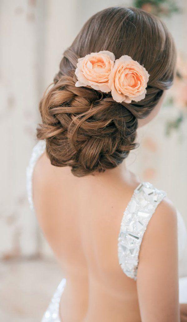 Peinados para el día de tu boda chica usando un chongo bajo con rosas color salmón como accesorio
