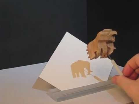 Small hand-carved wooden sculptures show fantastic shadows,   by artist and scientist John V. Muntean