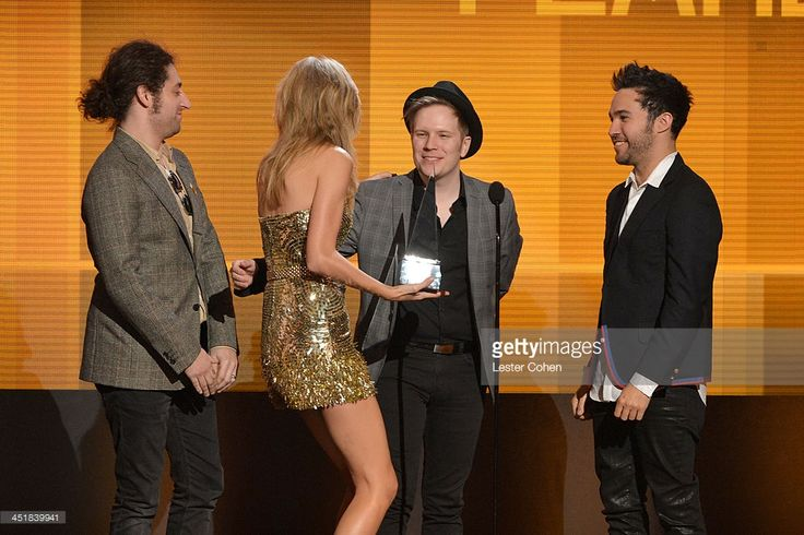 Recording artist Taylor Swift (2nd from L) accepts the Favorite Female Artist - Country Award from, (L-R), Joe Trohman, Patrick Stump and Pete Wentz of the band Fall Out Boy onstage during the 2013 American Music Awards at Nokia Theatre L.A. Live on November 24, 2013 in Los Angeles, California.