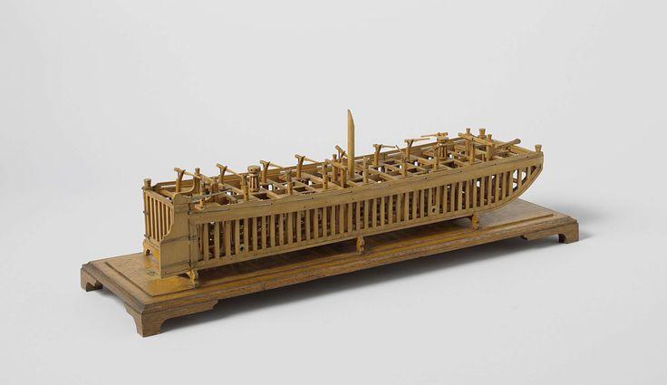 's Landswerf Rotterdam | Model van een scheepskameel, 's Landswerf Rotterdam, Rijkswerf Rotterdam, c. 1803 | Constructiemodel van een kleine scheepskameel, op een grondplank. De huid is weggelaten. De rechthoekige romp heeft een platte praam-achtige boeg. De kameel heeft zestien pompen in twee rijen, twee kaapstanders en twee betings, een kraanbalk bij de boeg, en vier spuien benedendeks, bediend met avegaar-achtige sleutels bovendeks, om de kameel vol te laten lopen. In het midden is een…
