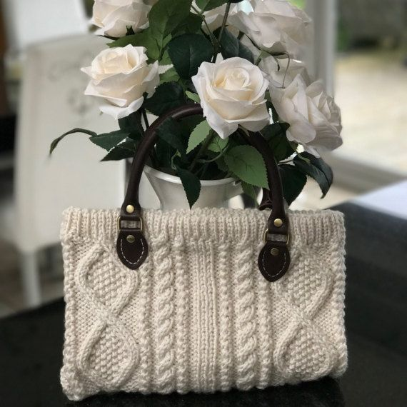 Soft wool blend Aran pattern handbag with leather handles. Knitted with a soft wool blend and lined with soft cotton fabric. The handle is approx. 35cm long. The bag measure approx. 30cm x 20cm I hand knitted this bag, then lined and finished the bag by hand.
