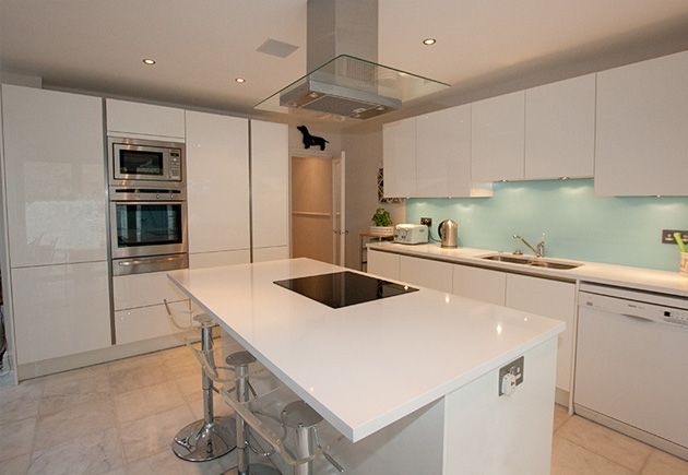 This stylish white kitchen island with breakfast bar seats 3 and has an overhang for neatly storing seating underneath when not in use. Other island features include a freestanding fridge, ceramic hob, roof-mounted island chimney hood and a secret drawer.