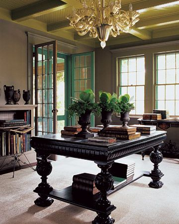 In this library, a white Jacobean-style table is painted black, making an elegant, functional library table. Large windows and french doors admit light. Love the aqua color on the exterior of the doors.  (Martha Stewart)