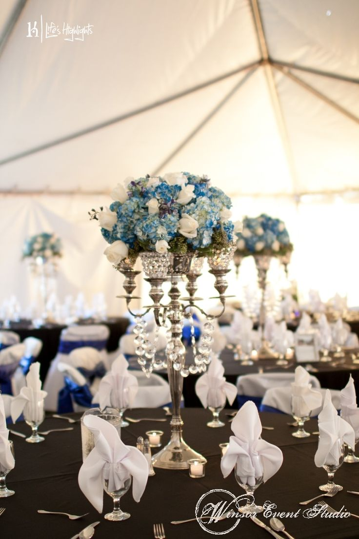 Centerpieces of silver candelabras with blue hydrangea