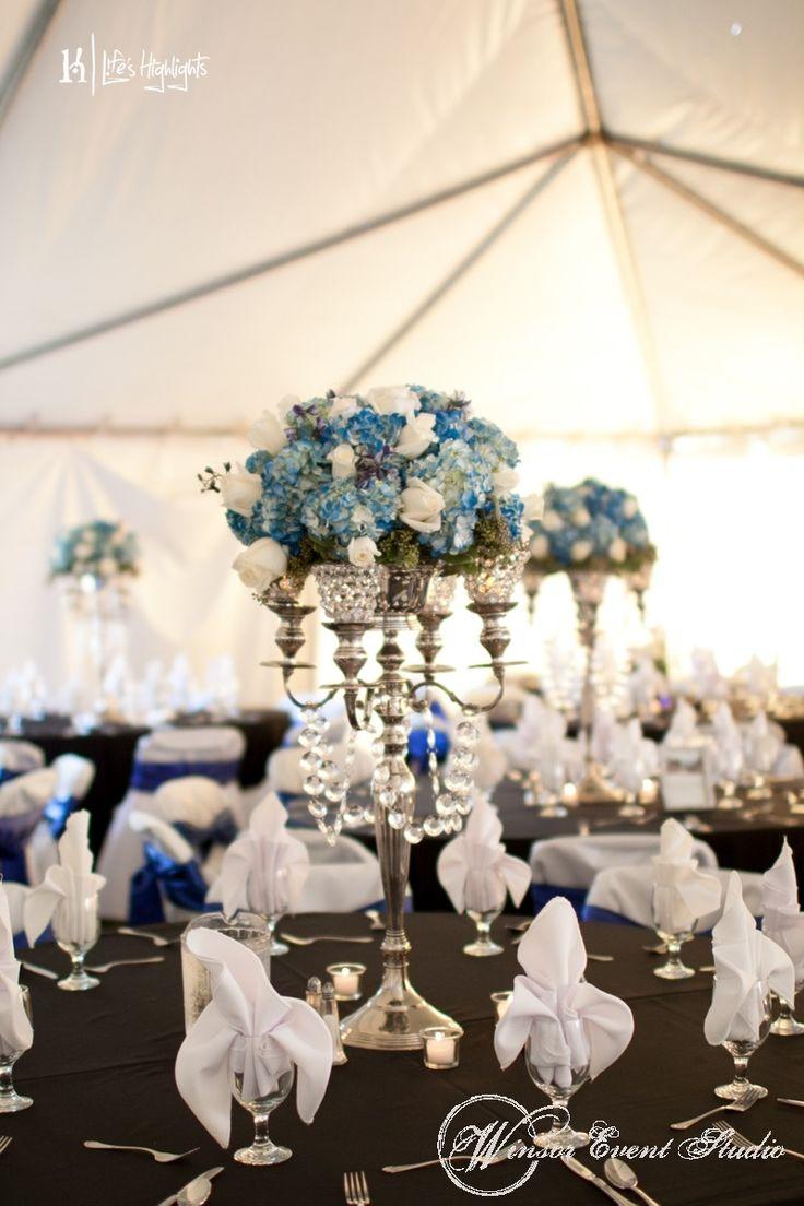 Centerpieces of silver candelabras with blue hydrangea