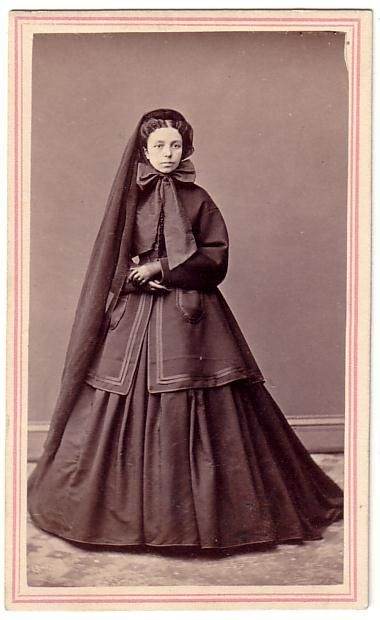 Early/mid 1860s. Her long, plain veil indicates that she is in one of the earlier stages of mourning.