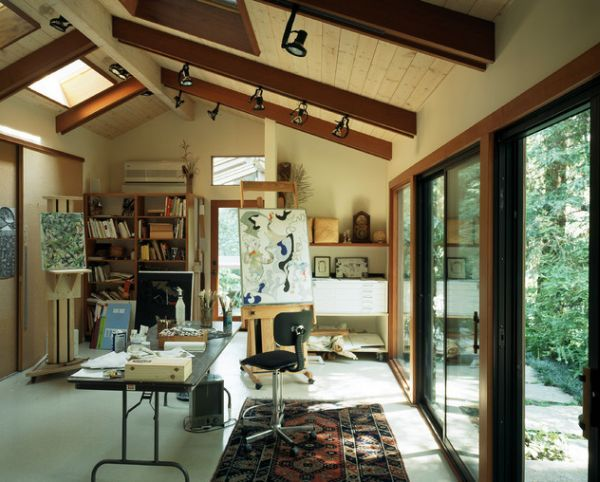 This contemporary home office is also quite interesting. It has an eclectic interior décor. There's a rather traditional area rug on the floor, exposed beams in the ceiling and large windows. The roof windows are also present like in the case of most artist's studio we've seen so far.