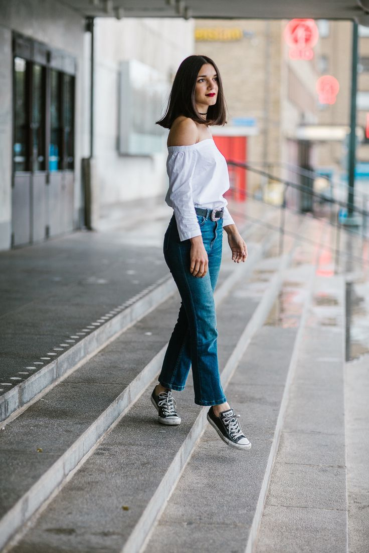 Anisa Sojka styles white Dorothy Perkins off the shoulder bardot top | Blue high-waisted H&M denim cropped flare jeans | Dainty silver and gold peace sign and evil eye necklaces | Black thin velvet choker | Black western belt with silver buckle | Leather Chuck Taylor Converse trainers with white laces | Red MAC matte lipstick | Dark short brunette straight hair | Fashion blogger street style shot in Gothenburg, Sweden by Mikaela Watsfeldt & Mikael Miettinen