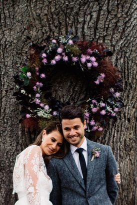 The newlyweds in front of a stunning wreath by Looseleaf florists after their ceremony under the oaktree at the Farm. Rustic Collingwood Children's Farm034