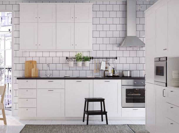 Vitt medelstort kök med svarta bänkskivor, handtag och knoppar. Här med köksfläkt, ugn och mikrovågsugn i rostfritt stål.
