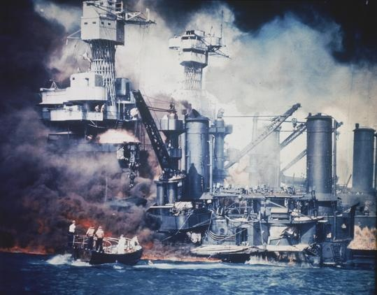 FILE - In this U.S. Navy file photo, a small boat rescues a USS West Virginia crew member from the water after the Japanese bombing of Pearl Harbor, Hawaii on Dec. 7, 1941 during World War II. Two men can be seen on the superstructure, upper center. The mast of the USS Tennessee is beyond the burning West Virginia. On Dec. 7, 1941, Japanese Imperial Navy navigator Takeshi Maeda guided his Kate bomber to Pearl Harbor and fired a torpedo that helped sink the US
