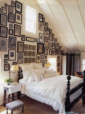 Framed wall in an attic/spare guest room with b&w antique family photos