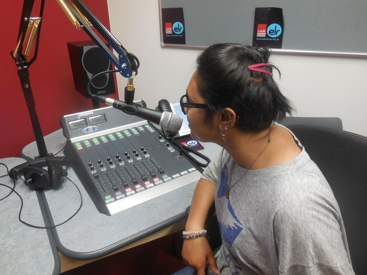 Participants learning how to use the microphone in a radio studio
