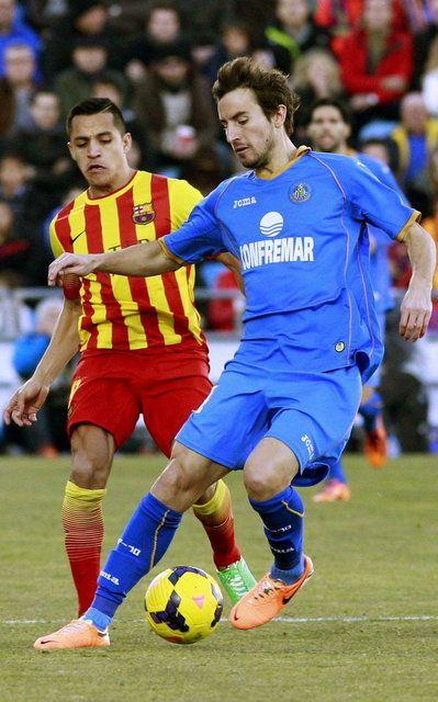 El centrocampista del Getafe Pedro Mosquera pelea un balón con el delantero chileno del Barcelona Alexis Sánchez