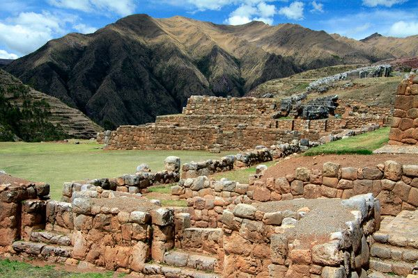 Sunlight upon the destroyed and eroded limestone construction of the Inca Empire - Chinchero Ruins - with the Hatun Luychu Mountain (partially cloud-shaded), along the Cordillera Vilcanota - Cusco department.