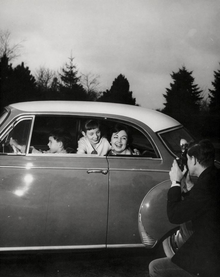50s black and white vintage photograph. Father takes a photo of the happy family in the car.