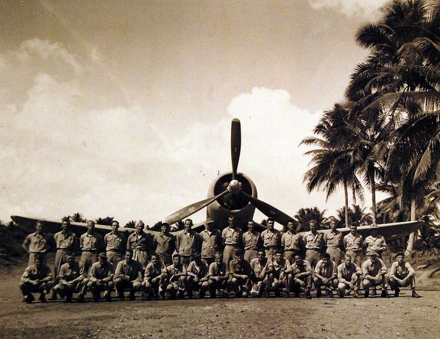 "Marine Attack Squadron Two Hundred and Fourteen - VMF 214 (Black Sheep Squadron) on Turtle Bay Fighter Strip, Espiritu Santo, New Hebrides. They are shown before leaving for Munda, with an F4U in the background, 11 September 1943. Note, Major Gregory ""Pappy"" Boyington, 8th from left, front row. U.S. Navy photograph, now in the collections of the National Archives."