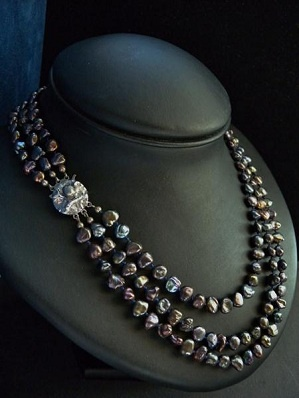 Cultured black fresh water pearl necklace in three rows of pearls, the colours varies from slightly green, red, petrol blue and navy blue.