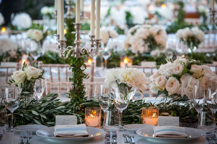 Table set up : high silver candlelabras, white roses, green runner made of olive brunces and of course warm candles!!!