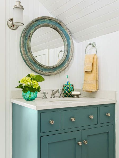 vanity painted green with a white countertop and sink, and a round, distressed green mirror, and a single sconce, hanging above