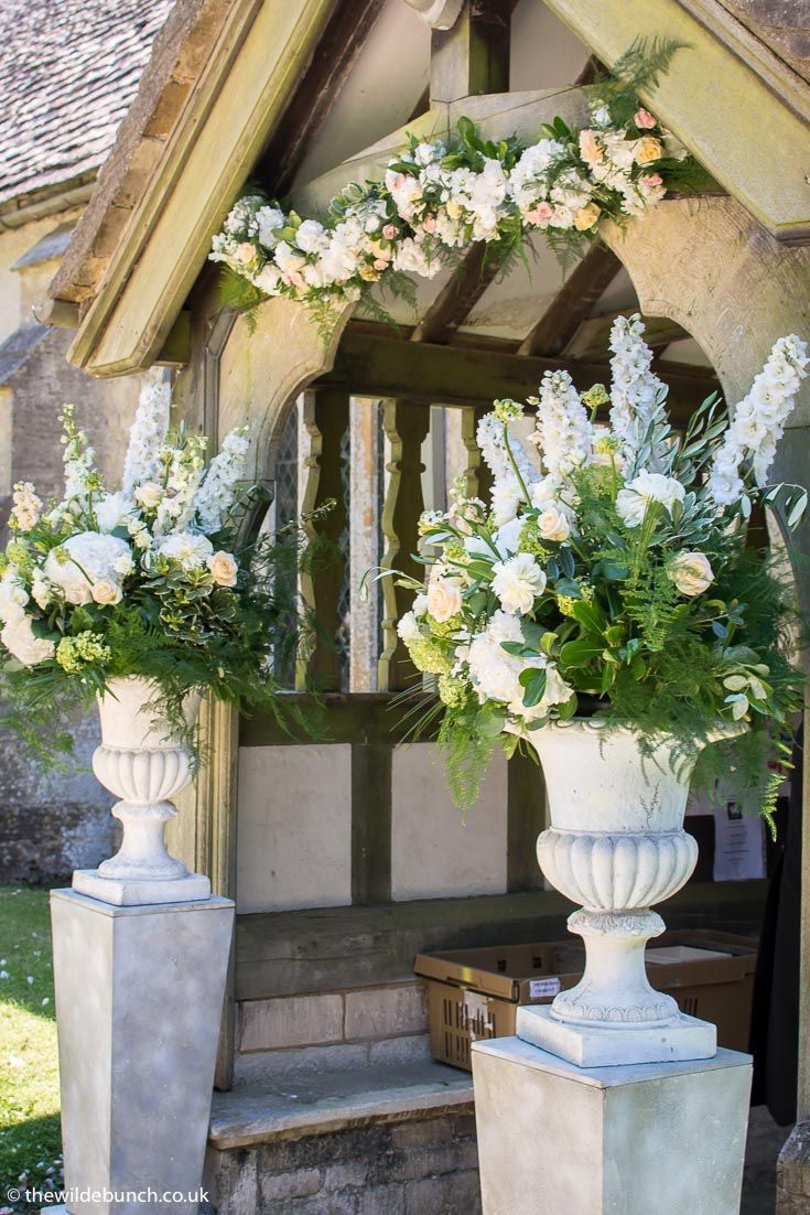 Spectacular church entrance flowers at Elmore Church. A Wilde Bunch design using our own plinths & Urns and a matching hanging garland over the arch